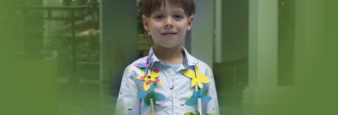 Junge mit gebastelter Blumenkette aus Papier.