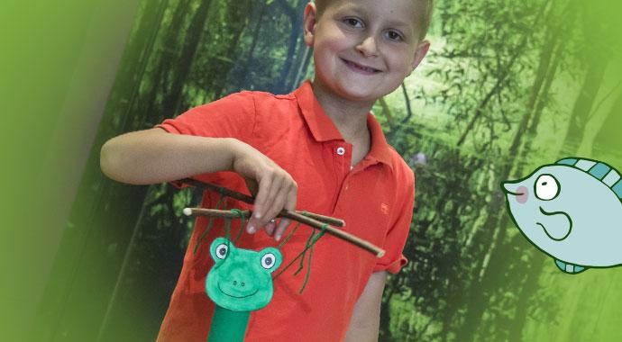 Junge hält in der rechten Hand eine gebastelte Marionette. Die Marionette ist ein Frosch.