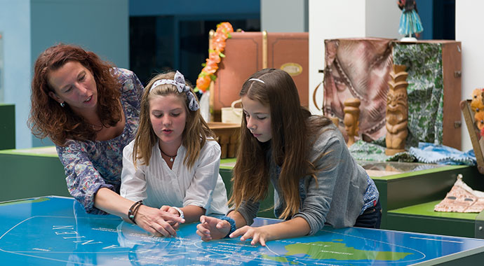 Woman and two girls look at a world map with Oceania section