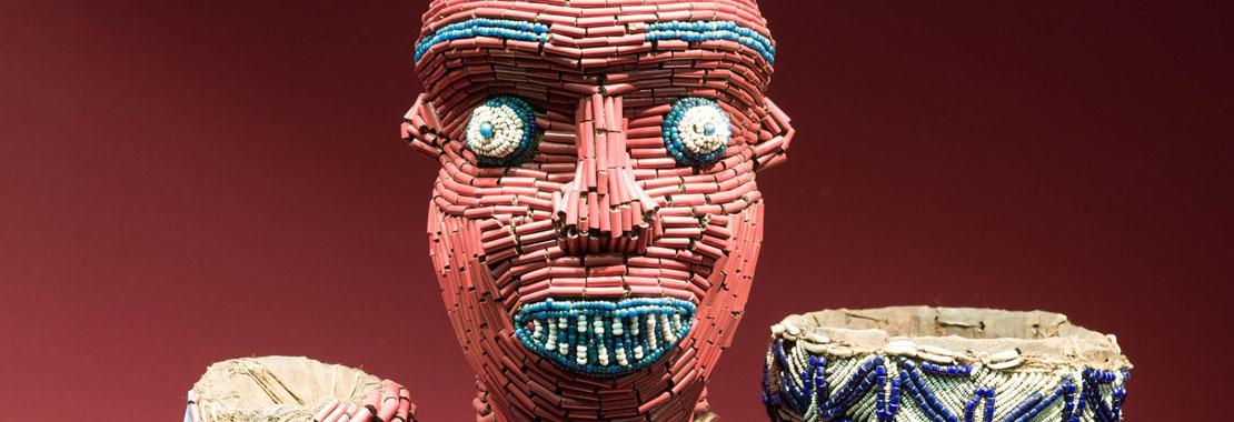 Close-Up von einer afrikanischen Figur, die mit vielen Perlen besetzt ist