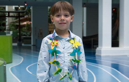 Ein Junge trägt eine selbst gebastelte Blumenkette