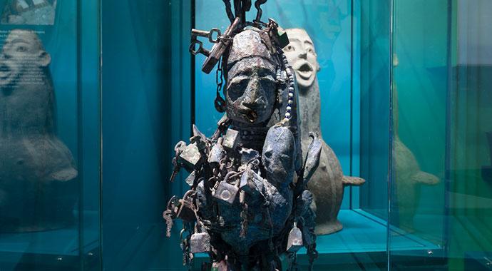 Skulptur einer Person behangen mit Schlössern und anderen Gegenständen aus Afrika