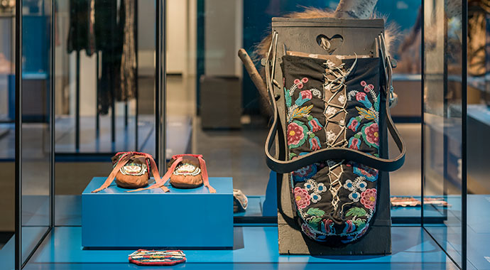 Display case with richly embroidered bag and mochassis on a pedestal.