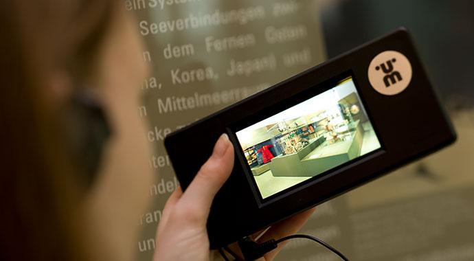 Blick auf ein mobiles Gerät und eine Hand