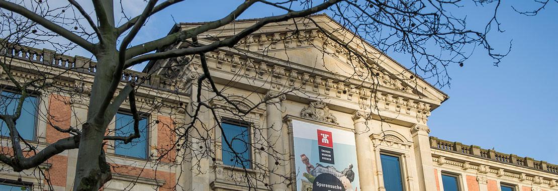 Fassade des Museums mit einem Baum davor und blauem Himmel