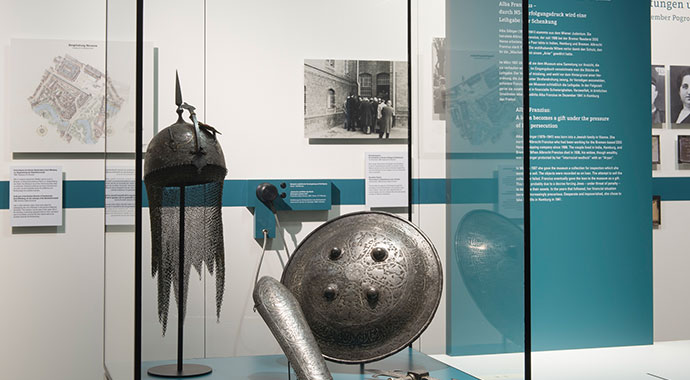 Glass showcase with helmet, shield and metal weapon, right next to it a board with exhibition texts