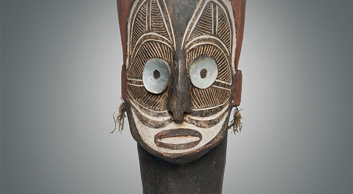 Wooden figure with large eyes of nacre