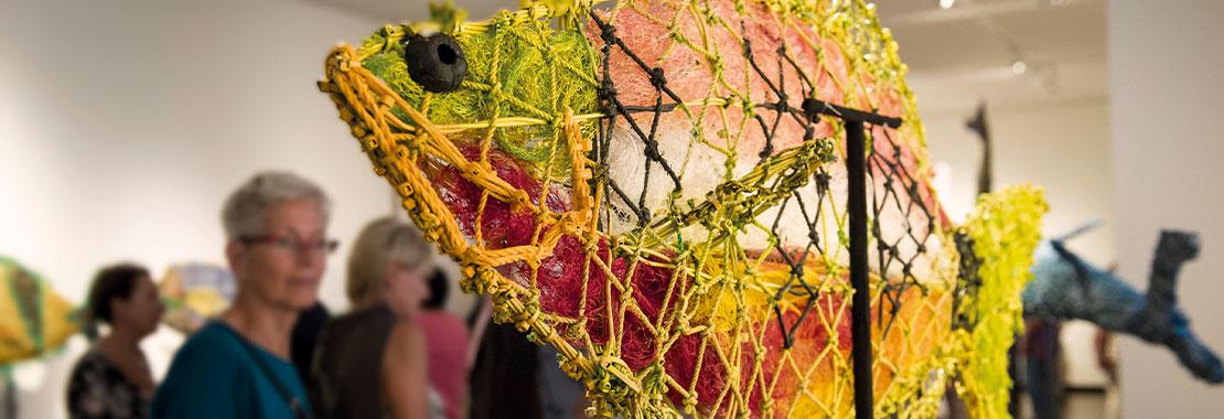 Foto von einem Ausstellungsbesuch, im Vordergrund Kunst aus geborgenen Plastikfischernetzen