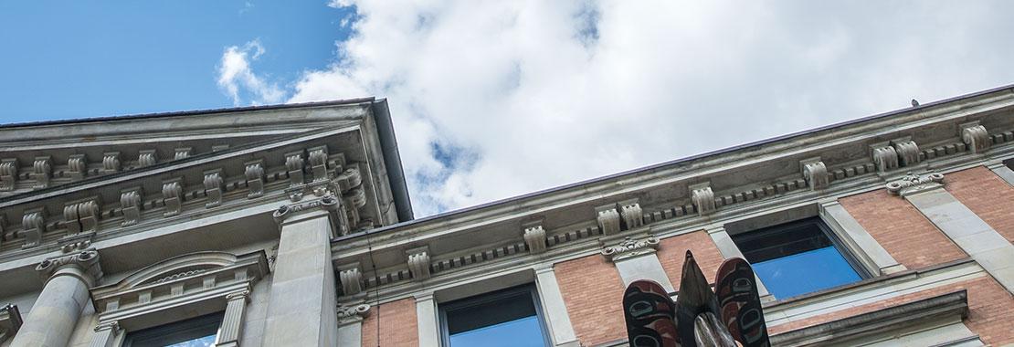 Detail der Hausfassade mit Totempfahl und blauem Himmel mit Wolken.
