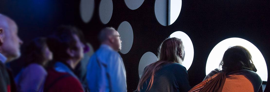 Mehrer Besucher blicken durch runde Ausschnitte in einer Wand und sehen so einen Film.