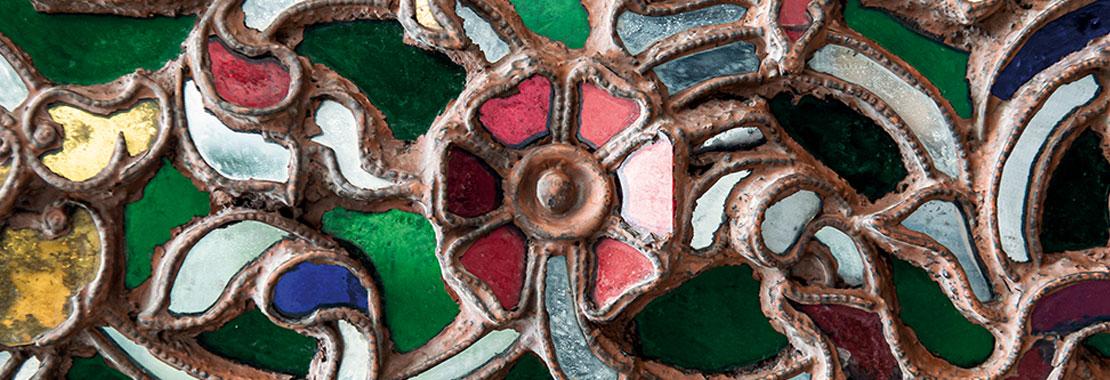 Florales reliefartiges Muster aus farbigen Glassteinen.