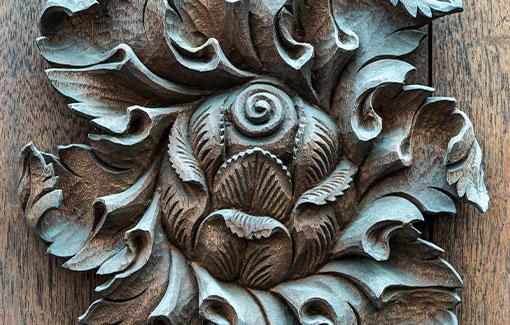 Geschnitztes Holzelement in kreisform aus einer Blüte und Blättern.