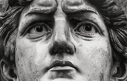streng schauender Kopf einer steinernen Statue
