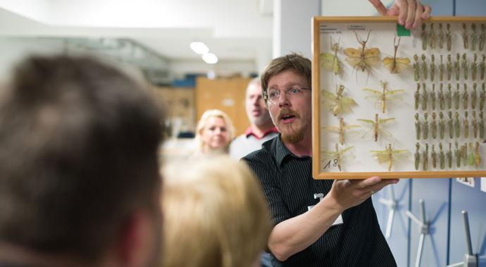 Ein Mann hält einen Insektenkasten in die Höhe und erklärt etwas