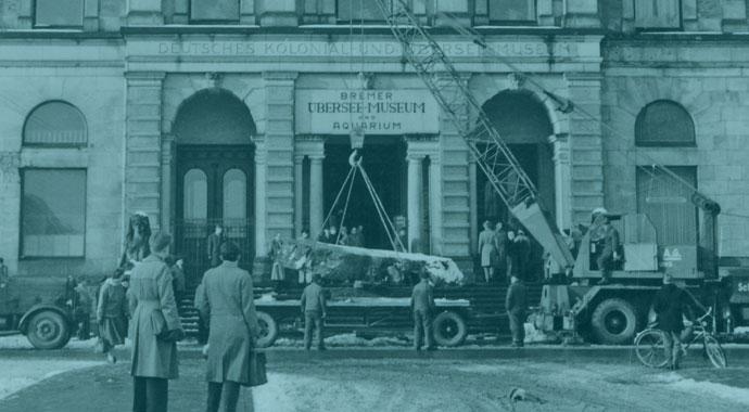 Vorplatz vor dem museum mit Menschen und einem Kran an dem eine Baumscheibe hängt.
