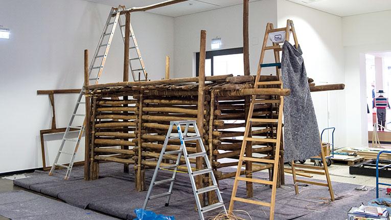 Aufbau eines Raumeinnehmenden Objektes aus Pfählen. Um das Objekt stehen Leitern und Werkzeug ist sichtbar.